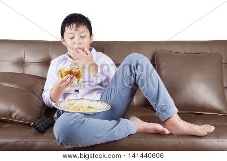 Cute little boy eating hamburger while sucking his finger and sitting on the sofa isolated on white background