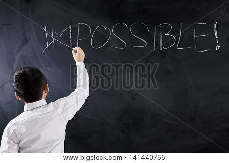 Male elementary school boy putting a cross over impossible on the chalkboard shot in the class