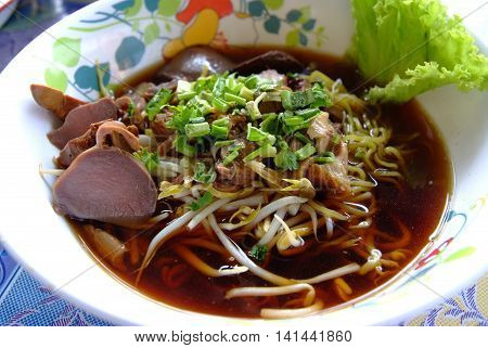 Egg noodles served with duck in a bowl.
