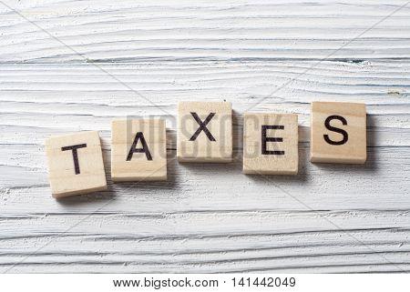 Taxes word written on wood abc block.