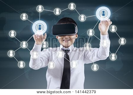 Little boy wearing virtual reality glasses and touch virtual network button on the virtual screen