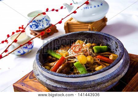 Freshwater eels braised with chili vegetables and herbs in chinese stew with tea pot on wooden table