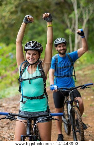 Excited athletic couple standing with mountain bike in forest