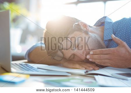 Male business executive yawning in office