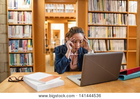 Tensed young woman using laptop in library at college