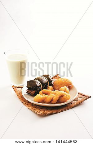 Fried crispy baked asian cake with glass of milk on white background