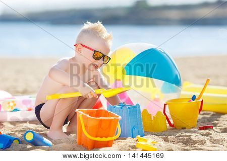 A little boy with short hair and blond hair, dark mirrored sun glasses, plays alone in the sand with a yellow shovel,orange and blue bucket and other toys, on the shore of the blue ocean