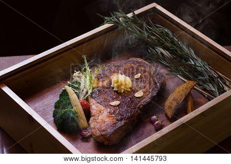 Roast smoked Angus eye steak on wooden box in black background