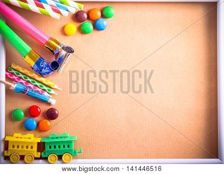Kids birthday party items over brown paper background