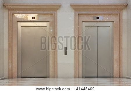 Two closed elevators in the shiny building
