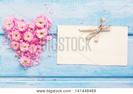 Background with heart from pink flowers and petals and empty tag on blue wooden planks. Selective focus. Place for text. Toned image.