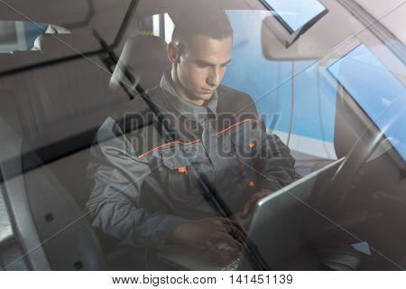 Repairman Examining Car