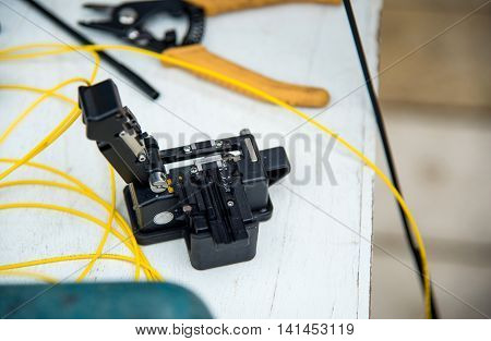 Cleaver optic fiber with pliers on white table.