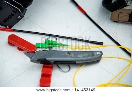 Fiber optic Pigtail with Cutter and shrink tube on white floor.