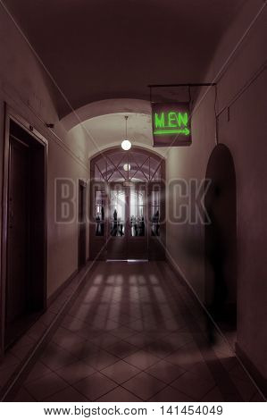 gloomy corridor with glass door behind which the hand