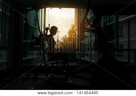 young fitness woman execute exercise with exercise-machine Cable Crossover in gym. young fitness woman execute exercise with exercise-machine Cable Crossover in gym, silhouette photo.