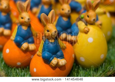 numerous colorful ceramic Easter bunnies sitting on colorful Easter eggs