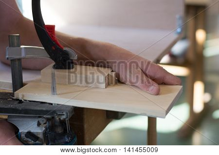 Carpenter sawing piece of wood with jigsaw