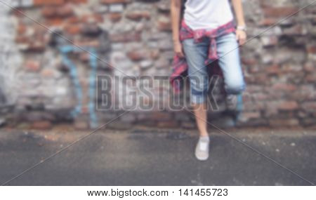Blurred lifestyle portrait of stylish young person in casual clothes: white t-shirt, plaid shirt, blue jeans and gray sneakers standing against urban brick wall background.