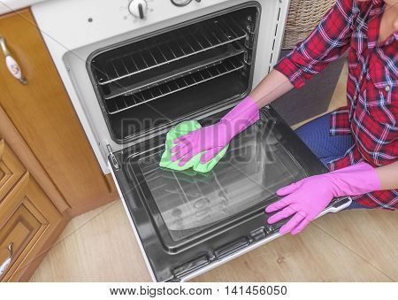Wash the oven door. Women's gloved hands are washed the dirt.