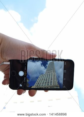 NEW YORK NY - AUGUST 4th 2016: Apple iPhone 6 held in one hand with camera showing Empire State Building in viewfinder