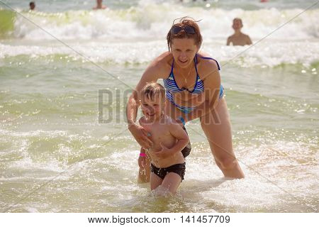 Mother Giving Son A Swimming Lesson In Sea With Waves During Summer