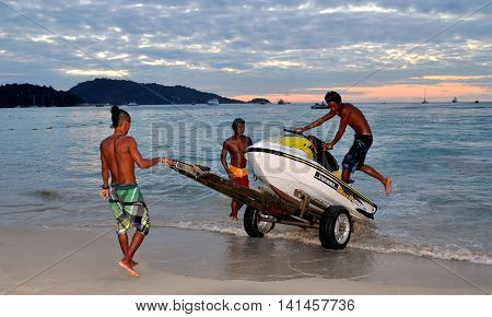 Phuket Thailand - January 3 2012: Thai beach boys load a jet ski onto a wheeled carrier at the end of a day on Patong Beach
