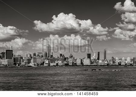 Manhattan Midtown West skyscrapers and Hudson River with passing clouds in Black & White. Cityscape of a summer afternoon in New York City with view of Midtown and West Village