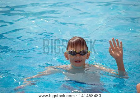 boy in blue spectacles for swimming swims in the sea. blue sky. hot summer