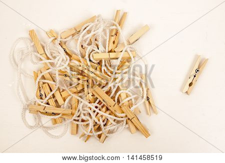 Wooden clothespins on a white rope and one clothespin isolated near them on light background. Washing and drying laundry at home.