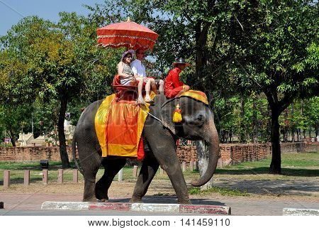 Ayutthaya Thailand - December 20 2010: Tourists accompanied by a mahout trainer enjoy an elephant ride through the Ayutthaya National Historic Park
