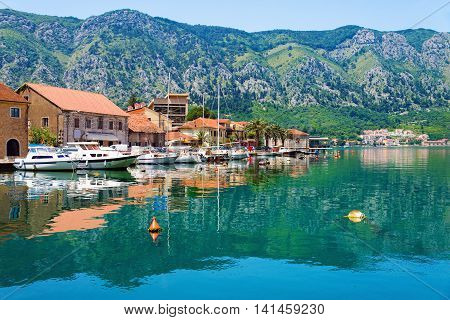 Kotor coastal town old Mediterranean port in secluded part of Bay of Kotor (Boka Kotorska) with yachts and fishing boats Montenegro. Mirror Adriatic Sea surface and idyllic seascape.