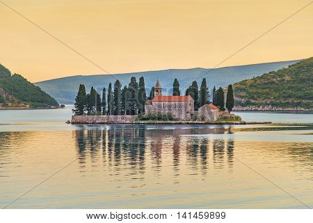 Island of Saint George (Ostrvo Sveti Dorde St.George) at sunset natural island in Adriatic sea one of the two islets off coast of Perast in Bay of Kotor Montenegro. Tourist travelling attraction.