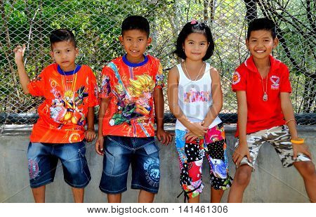 Hua Hin Thailand - December 31 2009: Four young children wearing clothing with western designs at the Khao Hin Lek Fai (Flintstone Mountain) lookout view point