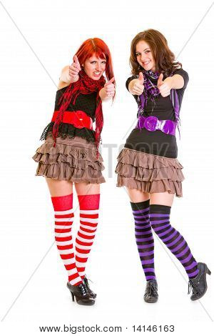 Two smiling young girlfriends showing thumbs up gesture isolated on white