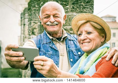 Senior couple taking a selfie inside a castle - Two persons in the 60's having fun with new technologies outdoor - Concept of active elderly - Focus on woman's face - Soft vignette