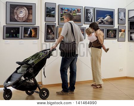 MOSCOW, RUSSIA - July 17, 2016: Family with elementary age girl and pram in a gallery. Classic Photo Gallery. Russian Week Of Photography 2016. July 17, 2016 in Moscow, Russia