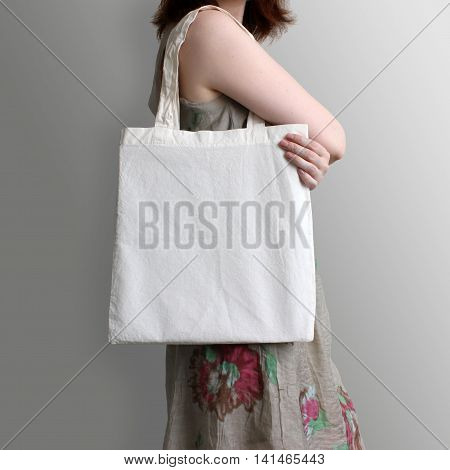 Girl is holding blank cotton eco tote bag design mockup. Handmade shopping bag for girls.