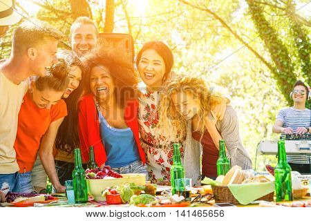 Group of young people having barbecue dinner party with dj in park - Multiracial cheerful friends laughing and toasting beers - Concept of positive mood with friends - Soft focus on black girl's face