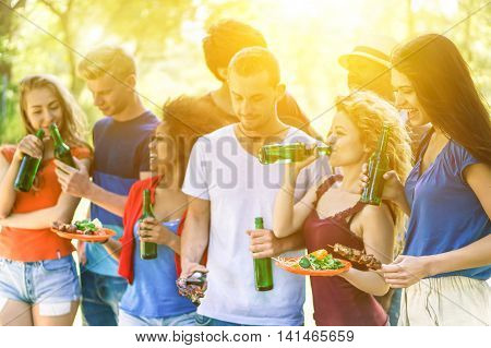 Group of multi-ethnic friends having barbecue meal outdoor on park with back lighting - Young cheerful people enjoying bbq on summer time - Friendship concept - Focus on right girl