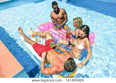 Young people drinking cocktails and having fun in swimming pool party - Cheerful friends enjoying vacation on hotel resort - Summer and holiday concept - Focus on bottom man - Top view - Warm filter