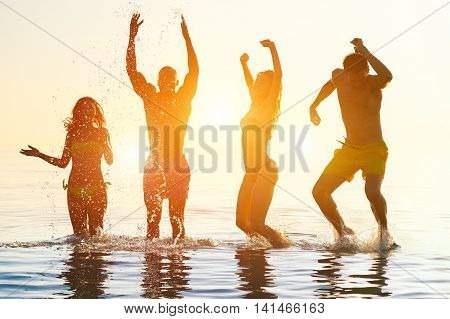 Young people swimming at sunrise party on the beach - Group of multi race friends having fun on vacation - Friendship and holidays concept - Soft focus on right girl face - Soft vivid filter