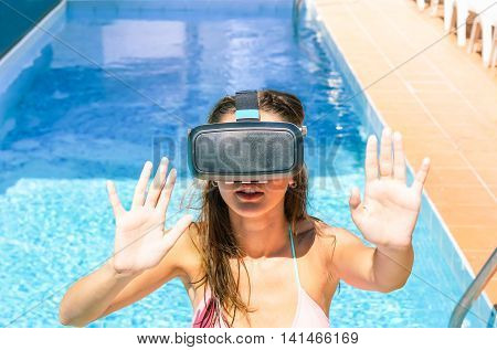 Close-up shot of young woman dressed in a glasses of virtual reality in hotel swimming pool - Girl using new smartphone tools - Technology addiction and vacation concept - Warm filter