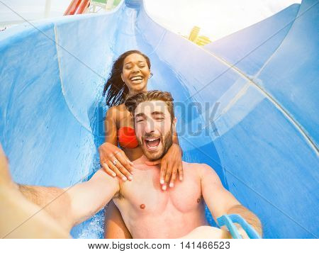 Young happy friends having fun in aqua park pipe - Cheerful multi race couple taking selfie photo with funny faces - Vacation and love concept - Soft focus on man face - Warm filter