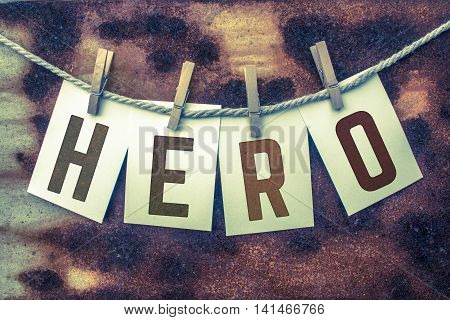The word HERO stamped on card stock hanging from old twine and clothes pins over a rusty vintage background.