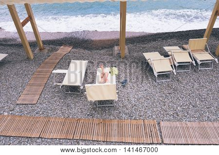 lonely woman lies in a lounge chair by the sea