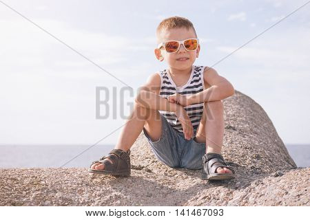 little boy in sunglasses sitting on a concrete breakwater on the sea background