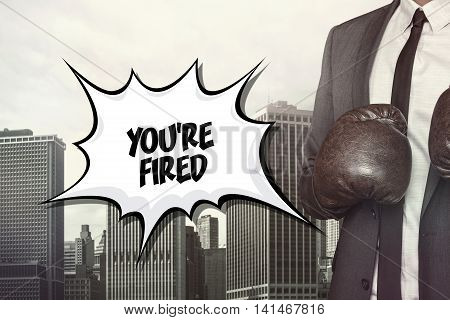 Youre fired text on speech bubble with businessman wearing boxing gloves