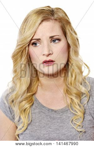 Sad or frustrated blond woman looking to the side. Disappointed young woman, isolated on white background.