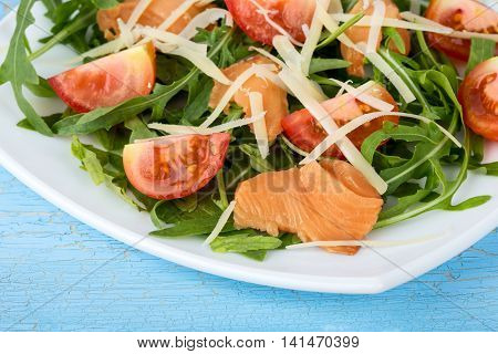Close up view of fresh salmon salad with cherry tomatoes and sheese on blue wooden background